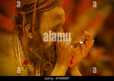 Indian naga baba sadhu lights chillum in 2013 Kumbh Mela in Allahabad (Prayaga) - Stock Photo