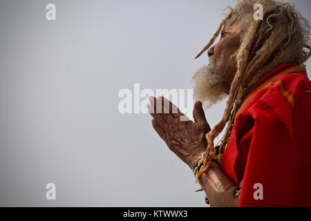 Kumbh Mela 2013 in Allahabad. Old Baba sitting at the shores of Sangham giving blessing and praying - Stock Photo