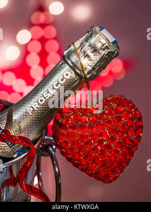 PROSECCO LOVE ROMANCE PARTY LIGHTS Prosecco bottle on ice in wine cooler with  party streamer & sparkling love heart - Stock Photo
