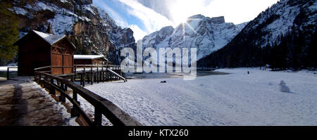 sun setting, with a beautiful reflection, behind the lake of Braies framed by the snow-capped mountains and the - Stock Photo