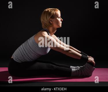 Young woman practicing yoga,  Paschimottanasana / Seated Forward Bend pose - Stock Photo