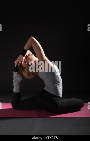 Young woman practicing yoga, Eka pada Rajakapotasana / Pigeon pose - Stock Photo