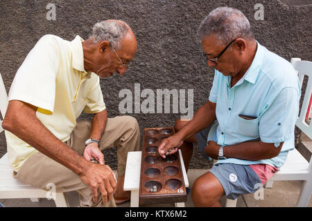 Local men playing the traditional board game ouril, also known as oware, uril,ouri,ori or mancara in the back streets - Stock Photo