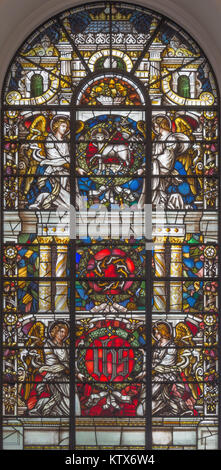 LONDON, GREAT BRITAIN - SEPTEMBER 14, 2017: The angels with the IHS initials and Lamb of God on the stained glass - Stock Photo