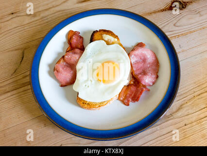 Simple lunchtime meal home cooked fried egg on toast with grilled smoked back  bacon - Stock Photo