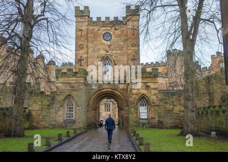 A man walking into the entrance to historic Durham Castle now part of the University in winter - Stock Photo