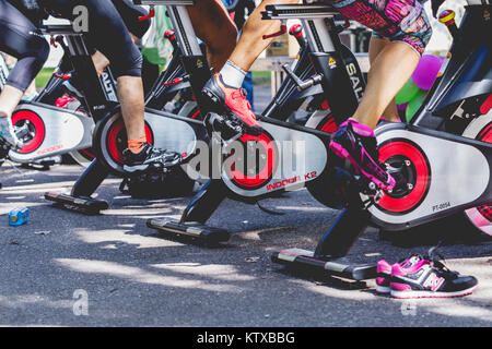 Zamora, Spain - September 02, 2017: People perform a spinning session outdoors in an urban park. Cycle Against Cancer. - Stock Photo