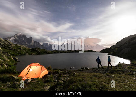 Hikers and tent on the shore of Lacs De Cheserys at night with Mont Blanc massif in the background, Chamonix, Haute - Stock Photo