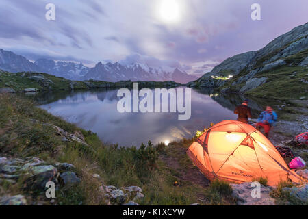 Hikers and tent on the shore of Lacs De Cheserys at night with Mont Blanc massif in background, Chamonix, Haute - Stock Photo