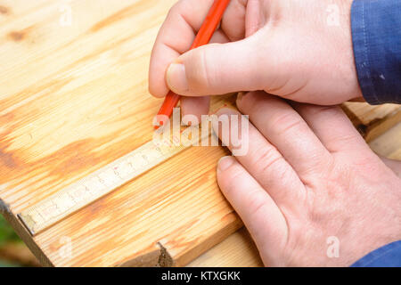 Craftsmen making a mark on wood for cutting - Stock Photo