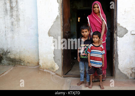 Young indian woman wearing sari and a veil over her hair with her kids at the door at their home, village near Pushkar, - Stock Photo