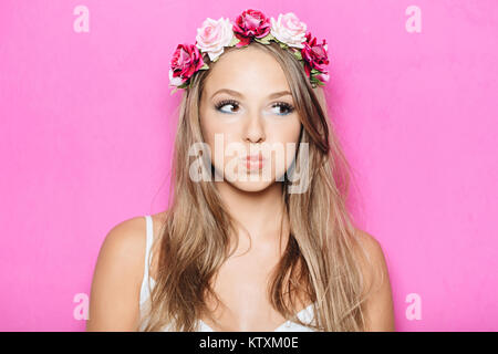 Funny pretty girl puffing out her cheeks against studio pink background. Headshot of charming blond young woman - Stock Photo
