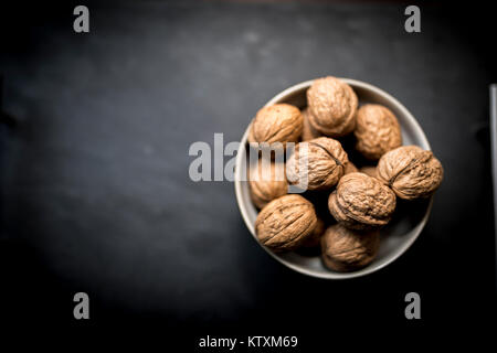 A bowl of whole walnuts in their shells in a bowl shot from above on a black slate background - Stock Photo
