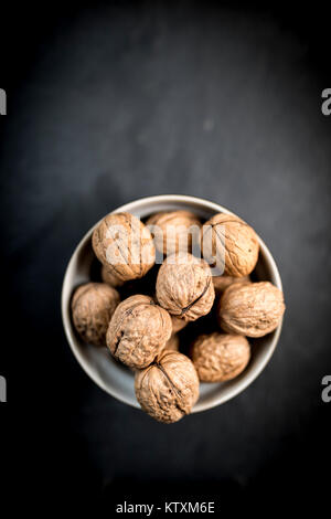 A bowl of whole walnuts in their shells in a bowl shot from above on a natural black slate background - Stock Photo