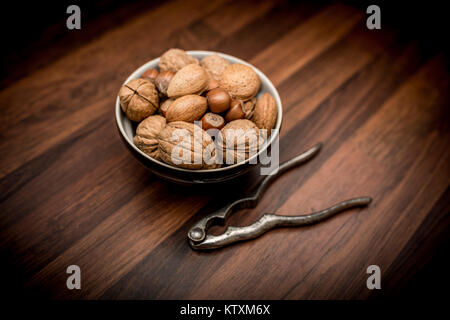 A bowl of mixed whole nuts in their shells including walnuts, hazelnuts, almonds and pecans with nut cracker - Stock Photo