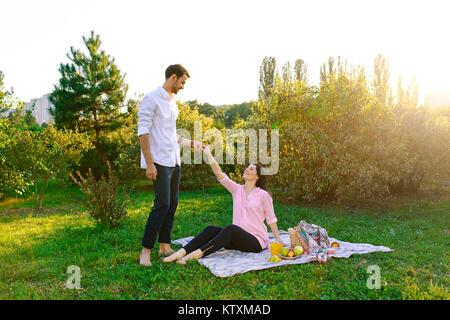 Happy pregnant couple in park on picnik - Stock Photo