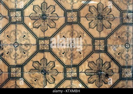 Old, discoloured, Portuguese azulejo ceramic tiles with a floral pattern, decorate the external walls of a building - Stock Photo