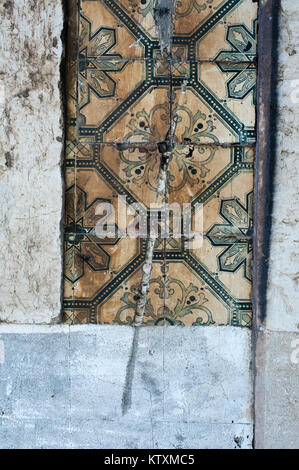 Old, damaged, Portuguese azulejo ceramic tiles with a floral pattern, decorate the external walls of a building - Stock Photo