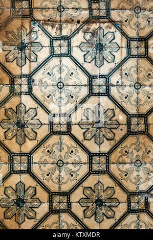 Weathered, Portuguese azulejo ceramic tiles with a floral pattern, decorate the external walls of a building in - Stock Photo