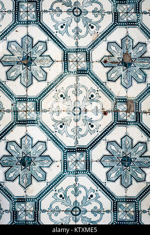 Old, worn, Portuguese azulejo ceramic tiles with a floral pattern, decorate the external walls of a building in - Stock Photo