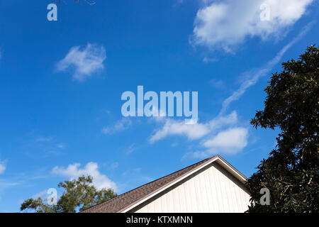Vivid blue skies with clouds, tree, rooftop and shadows in bright midday sun - Stock Photo