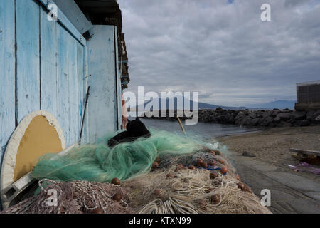 a black cat sleeping and washing him self under the shadow of the naple's volcano, the Vesuvio - Stock Photo