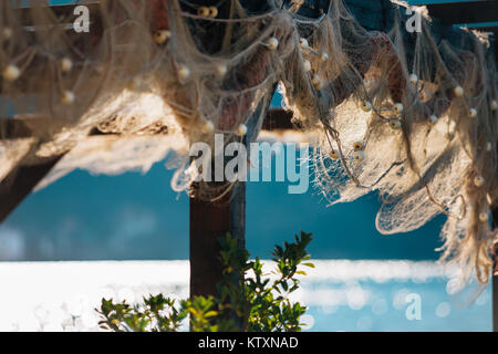 Old Fishnet Hanging on wooden construction at the Sunny day near the sea. - Stock Photo