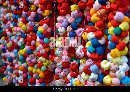 Colorful cloth balls Kukurizaru, monkeys with bound feet, representing control of desires in exchange for written wishes hanging at a shrine in Yasaka