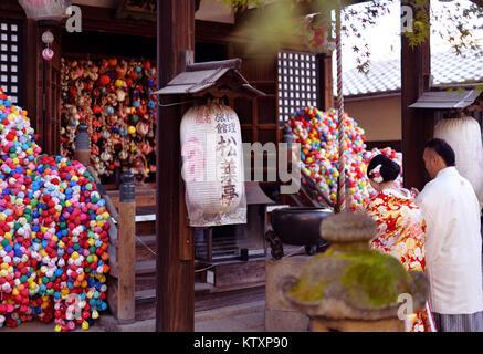 Couple wearing traditional kimonos praying at Yasaka Koshindo, Daikoku-san Kongo-ji Koshin-do a small temple in Higashiyama, Kyoto, Japan 2017.