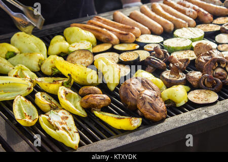 Assorted delicious grilled meats with vegetables over the barbecue on the charcoal. Sausages, steak, pepper, mushrooms, - Stock Photo