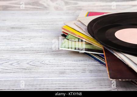 Old vinyl record on wooden background. Retro style - Stock Photo
