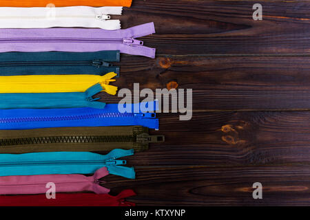 Multicolored zippers are laid out on a wooden table - Stock Photo