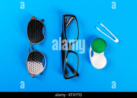A set of accessories for sight. Pinhole glasses, lenses with container and glasses for sight. Pair of medical pinhole - Stock Photo