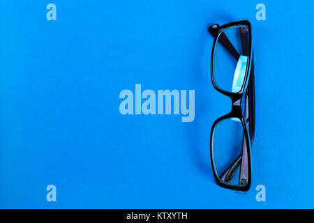 Modern fashionable and office spectacles on blue background, Perfect reflection, eye glasses on table for copy space. - Stock Photo