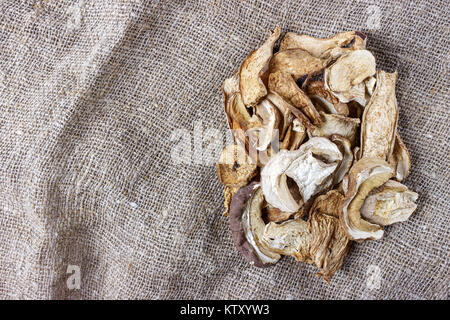 dried mushroom on sackcloth. Top view dried porcini mushrooms. - Stock Photo