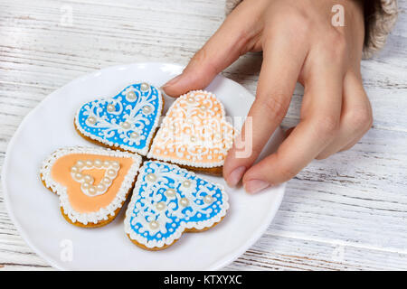 Hands hold cookies in form of heart. - Stock Photo