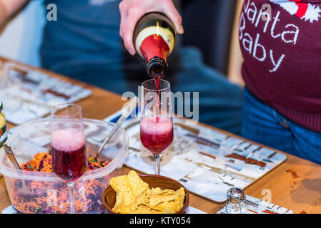 Pregnant female in christmas pullover holding bottle and pouring red non alcoholic wine into champagne glass on - Stock Photo