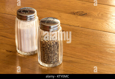 Close up of glass salt and pepper shakers or salt and pepper pots on a wooden table ,very common dining condiments - Stock Photo