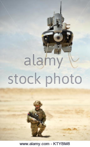 A soldier watches as a Tarantula Hawk (T-Hawk) Micro Remote Piloted Air System (RPAS) hovers over the desert in - Stock Photo