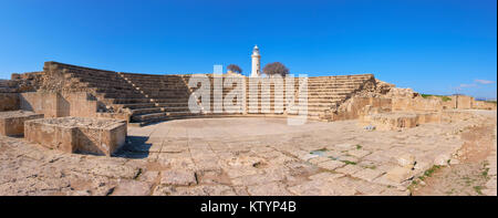 Ancient Greek amphitheater in archaeological site in Paphos, Cyprus, with a white lighthouse on the back, panoramic - Stock Photo