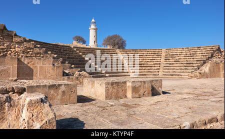 Ancient Greek amphitheater in archaeological site in Paphos, Cyprus, with a white lighthouse on the back - Stock Photo