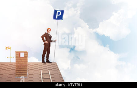 Young businessman with parking sign standing on brick roof. Mixed media - Stock Photo