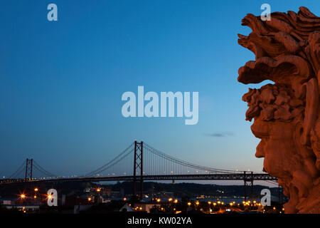 View of the 25 April Bridge (Ponte 25 de Abril) in Lisbon, Portugal. A sculpture stands in the foregrounds at the - Stock Photo