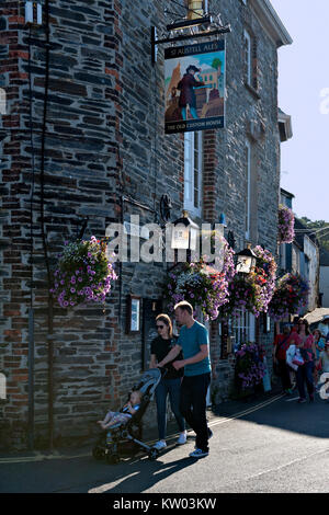 TA Couple pushing a small child in a pushchair pass The Old Custom House public house in Padstow, Cornwall. UK - Stock Photo