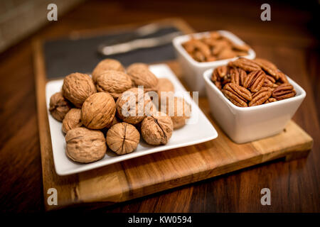 A healthy and nutritious selection of nuts on a wooden serving board with walnuts, pecans, and almonds in contemporary - Stock Photo