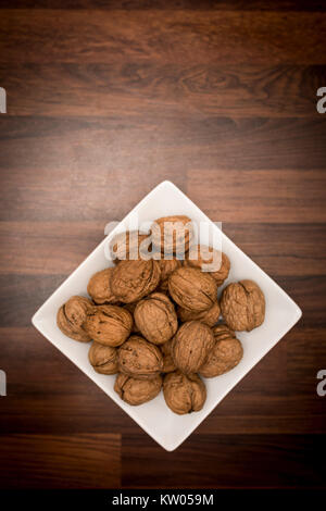 A bowl of whole walnuts in their shells in a white square bowl shot from above on a butchers block worktop - Stock Photo