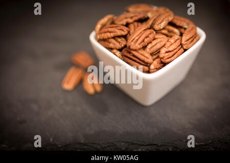 A white bowl of healthy and nutritious pecan nuts shot from above on a black slate background - Stock Photo