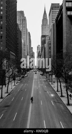 Great view on E 42nd street taken from Tudor City pl, lonely walker catched in the middle of street - Stock Photo