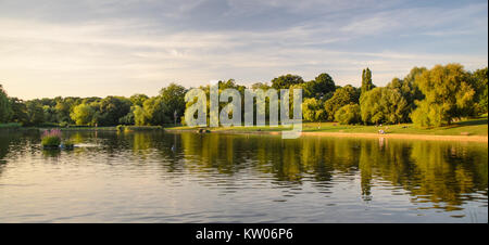 London, England, UK - August 20, 2013: People relax beside the Hampstead Ponds in Hampstead Heath park, North London. - Stock Photo