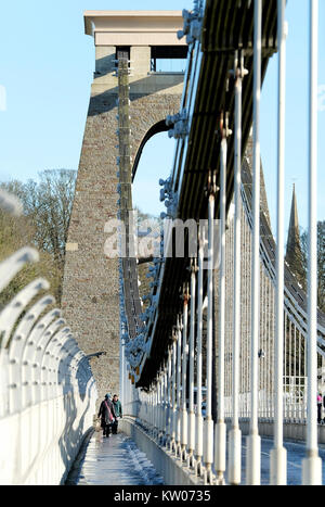 A woman carrying a large bag walking across the Clifton Suspension Bridge in Bristol, UK. A cold winter day and - Stock Photo